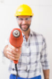 Construction worker holding power drill. In a new house Royalty Free Stock Photography