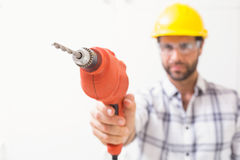 Construction worker holding power drill. In a new house Royalty Free Stock Image