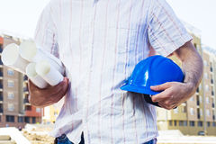 Construction worker holding project and blue hard hat Royalty Free Stock Photo