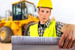 Construction worker holding project documents. Close up of a construction worker holding project documents at construction site Stock Photography