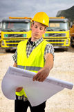 Construction worker holding project documents at construction site. Close up of a construction worker holding project documents at construction site Royalty Free Stock Image