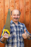 Construction worker holding a saw and showing thumbs up approval Stock Images