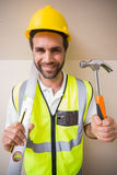 Construction worker holding spirit level and hammer Royalty Free Stock Photo