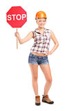Construction worker holding a traffic sign stop. Full length portrait of a construction worker holding a traffic sign stop on white background Royalty Free Stock Photo