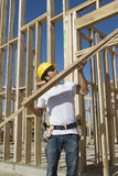 Construction Worker Holding Up Plank Royalty Free Stock Photos