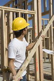 Construction Worker Holding Up Plank Stock Photo