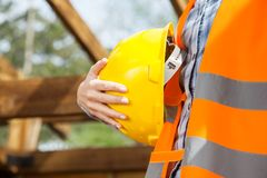 Construction Worker Holding Yellow Hardhat. Midsection of female construction worker holding yellow hardhat at site Stock Photos