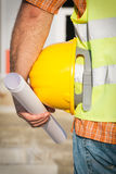 Construction worker holding yellow hardhat Royalty Free Stock Photo