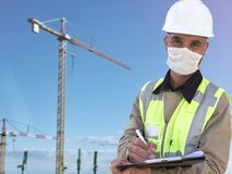 Free Construction Worker In White Hardhat And Protective Mask Stands With Clipboard Opposite Construction Site With Cranes Stock Image - 184304431