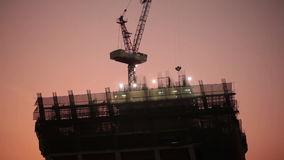 Construction worker at industry site, building development for skyscraper, taken on sunset scene, low angle view stock video footage