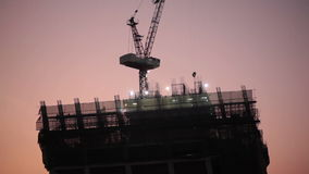 Construction worker at industry site, building development for skyscraper, taken on sunset scene, low angle view stock video