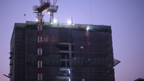 Construction worker at industry site, building development for skyscraper, taken on sunset scene, low angle view stock footage