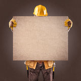 Construction worker with information posters on a brown backgrou Stock Photography
