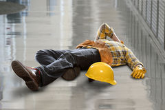 Construction Worker Injured After Fall. Injured construction worker laying on floor after fall Royalty Free Stock Photos