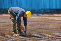 Construction worker installing binding wires. Authentic construction worker installing binding wires to reinforcement steel bars in construction site. Space for Royalty Free Stock Image