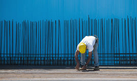 Construction worker installing binding wires. Authentic construction worker installing binding wires to reinforcement steel bars in front of a blue insulated Stock Photography