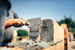 Construction worker installing brick masonry on exterior wall with trowel putty knife. Bricklayer construction worker installing brick masonry on exterior wall Stock Image