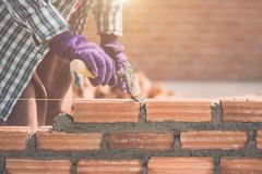 Worker installing bricks wall in process of house building royalty free stock image
