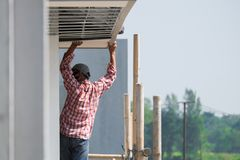 Construction worker installing ceiling board, exterior build stock images