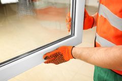 Construction worker installing new window. In house stock photos