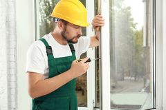 Construction worker installing new window. In house stock photo