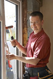 Construction Worker Installing New Windows In House. Portrait Of Construction Worker Installing New Windows In House Stock Image