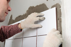 Construction worker installing tiles Stock Photos