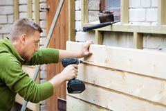 Construction worker installing wooden planks on house facade Stock Photos