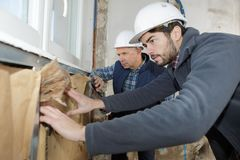 Construction worker insulating house walls stock photography