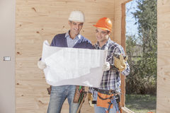 Construction Worker on the job. Looking at blueprints Stock Photo