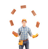 Construction worker juggling with bricks Stock Images