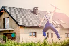 Construction worker jumping outside home Royalty Free Stock Image
