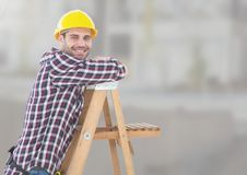 Construction Worker on ladder in front of construction site Stock Images