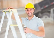 Construction Worker with ladder in front of construction site Stock Photo