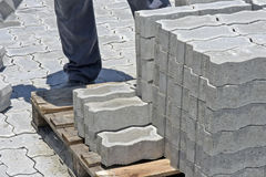 Construction worker laying concrete tiles to pave street Royalty Free Stock Images