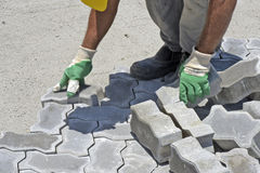 Construction worker laying concrete tiles Royalty Free Stock Images