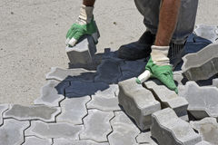 Construction worker laying concrete tiles Royalty Free Stock Image