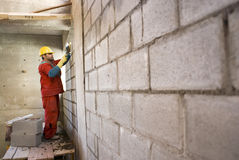 Construction Worker Lays Cinder Block - Horizontal Stock Image