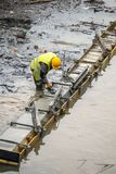 Construction worker leveling concrete formwork 2. Construction worker leveling concrete formwork in water for river bank repair. Concrete revetment. Color effect Royalty Free Stock Photography