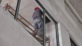 Construction Worker Lifts Gear Box for Fire Shutter stock video