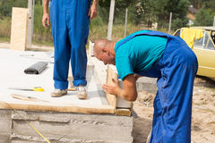 Construction worker lining up insulated walls Royalty Free Stock Photo