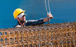 Construction worker loading beam cages Stock Image