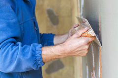 Construction worker with long trowel plastering a wall. royalty free stock photography