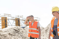 Construction worker looking at tired colleague wiping sweat at site Stock Image