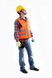 Construction Worker looking up. Serious construction worker in yellow helmet and orange waistcoat looking up. Full length studio shot isolated on white royalty free stock image