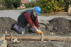 Construction worker making concrete foundation in formwork. Worker spreading concrete in formwork for wall foundation using trowel, real people working Royalty Free Stock Images