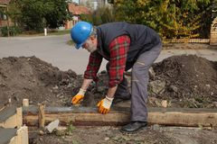 Construction worker making concrete foundation in formwork. Worker spreading concrete in formwork for wall foundation using trowel, real people working Stock Photos