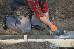 Construction worker making concrete foundation in formwork. Worker spreading concrete in formwork for wall foundation using trowel, real people working Royalty Free Stock Image