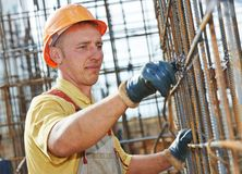 Construction worker making reinforcement. Builder worker knitting metal rods bars into framework reinforcement for concrete pouring at construction site Stock Photography