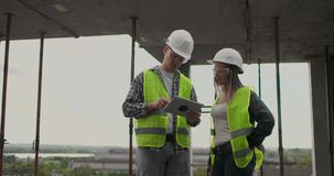 Construction worker man and architect woman in a helmet, discuss the plan of construction of house, tell each other stock footage